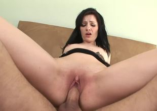 A raven haired girl is getting cumshot in her sexy little mouth