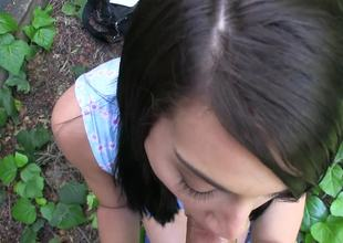 Dark haired sweetie sucks a big pecker outdoors for some cash