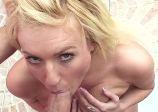 A blonde is displaying her large tits in the bathroom while sucking
